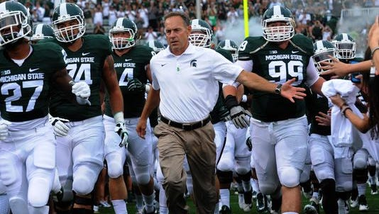 Mark Dantonio runs out on the field with his team for MSU's season-opener.