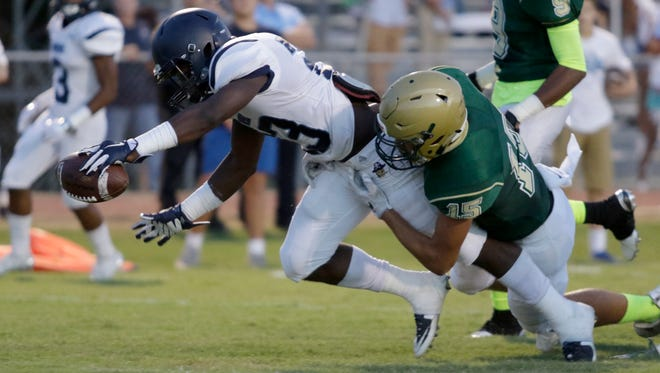Barbe running back Kirkland Banks drives for the goal line as he breaks through a tackle by Acadiana's Kanyon St. Julien on Friday at Bill Dotson Stadium.