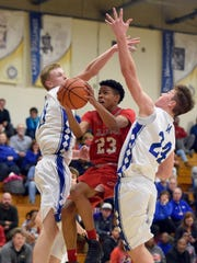 Jaylen Minor of Bosse tries to go up and under Sam DeVault of Memorial, left, and Branson Combs during the second quarter of the game at the Robert M. Kent Athletic Center in Evansville Tuesday.