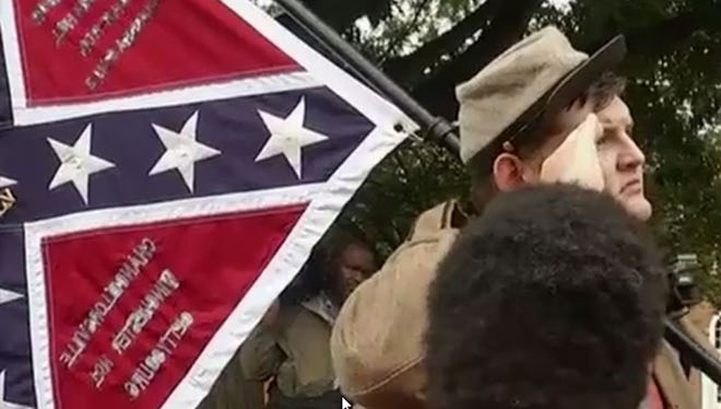Allen Armentrout, in Confederate uniform and carrying a Confederate flag, salutes the statue of Robert E. Lee in Emancipation Park in Charlottesville, Va., on Tuesday, Aug. 15, 2017.