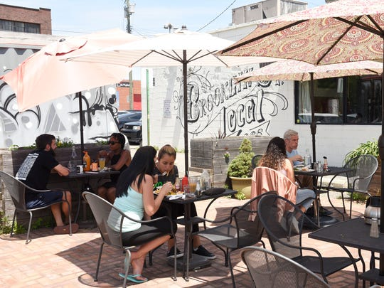 Customers eat on the patio at Brooklyn Street Local in Corktown. The restaurant is planning to expand its hours to meet growing demand. (Clarence Tabb Jr. / The Detroit News)
