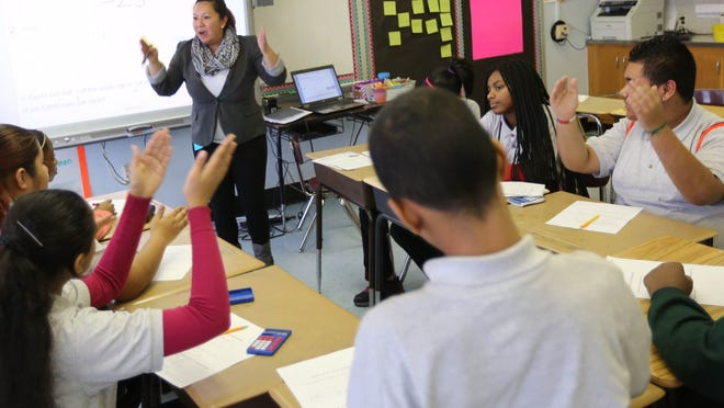 Julia Li leads her seventh grade math class in learning fractions at Eastside Charter School.