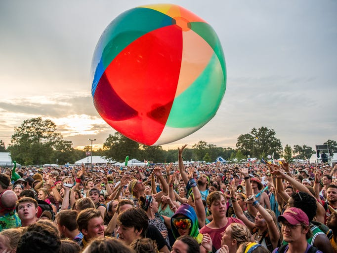 The crowd passes around a giant inflatable ball as