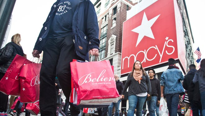 FILE - In this Friday, Nov. 27, 2015, file photo, shoppers carry bags as they cross a pedestrian walkway near Macy's in Herald Square, in New York. Thanksgiving Day shopping it isn't going away and some stores are rethinking their strategies on whether it makes sense to be open. Many major mall operators and big retailers such as Toys R Us, J.C. Penney, and Macy's are sticking with being open. Others, including the Mall of America, are closing for Thanksgiving.