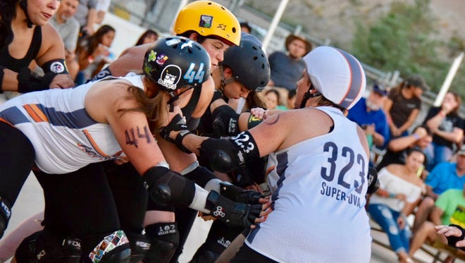 Members of the Crossroads City Derby Santas, in black, and the Los Alamos Derby Dames, in white, meet in a scrum during a bout July 8, 2017, at Meerscheidt Recreation Center.