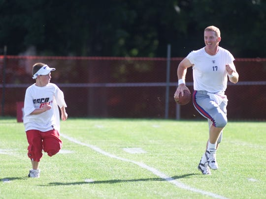 Giants QB Jason Garrett is chased by 11-year-old Jack Mara, the grandson of co-owner Wellington Mara, during a drill after an afternoon practice session on July 30, 2002.
