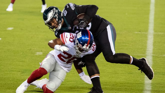 The Eagles' Richard Rodgers (85) is tackled by Giants' Julian Love (20) after making a reception Thursday night.