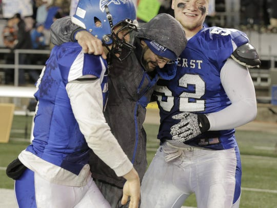 Amherst head coach Mark Lusic feels the long hours spent throughtout the year is worth be able to celebrate special moments with players Garrett Groshek (left) and Tyler Biadasz (52) after winning a  WIAA Division 5 championship in 2015.