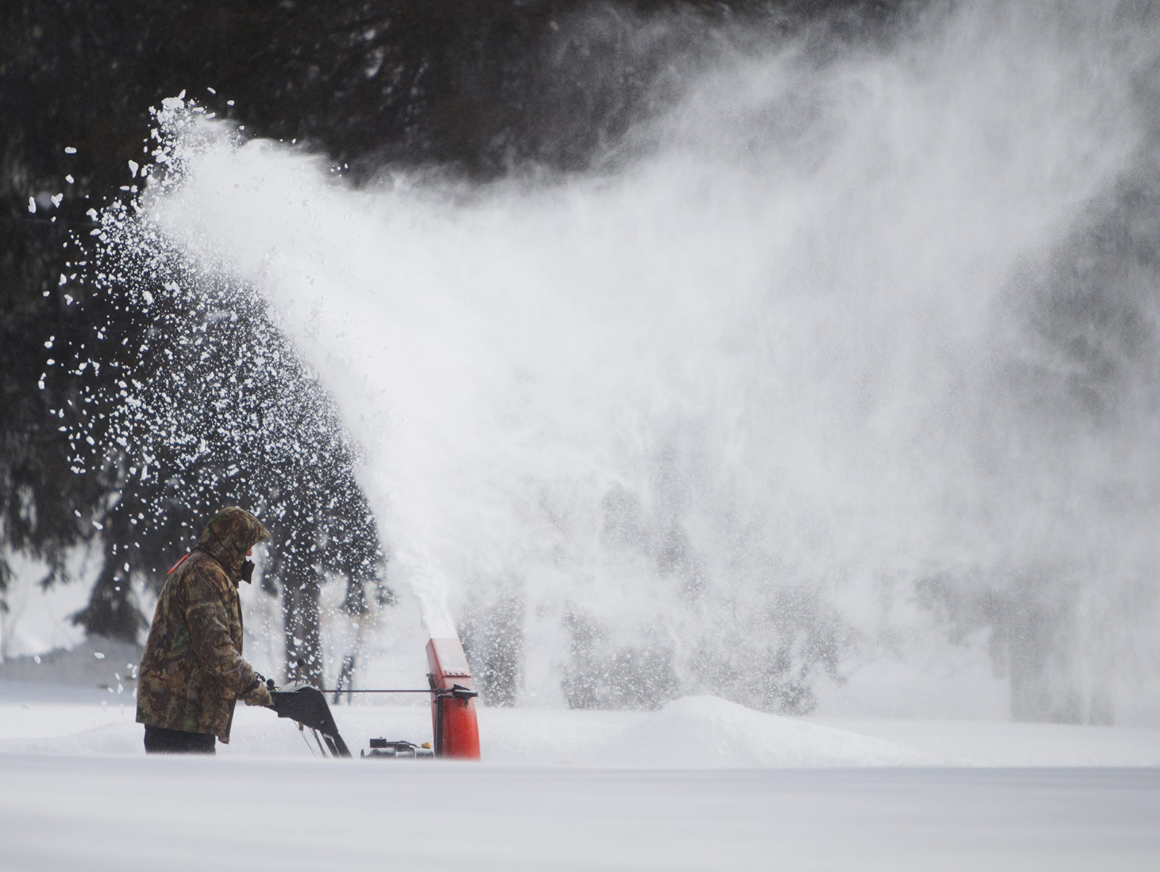 A man blows snow off his driveway along Browncroft