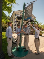 At Greenfield Village, from left, Eric Nelson, Jeff Nelson, Matthew Armstrong, and Kevin Kar work to set a pole outside Town Hall.