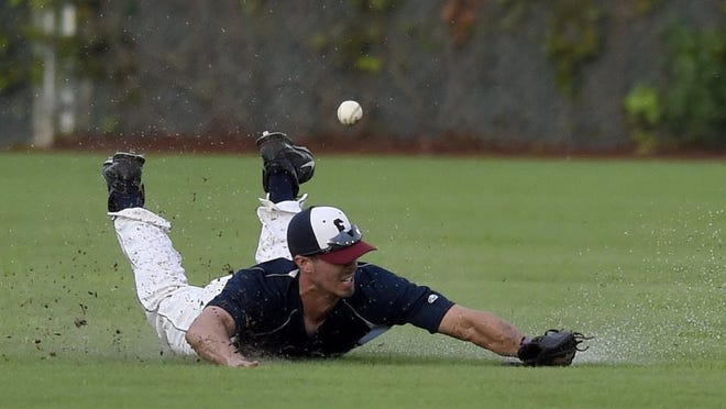 Otters center fielder Chris Sweeney dives for a ball as he lands in the rain-soaked outfield during the third inning of the game at Bosse Field in Evansville in July.