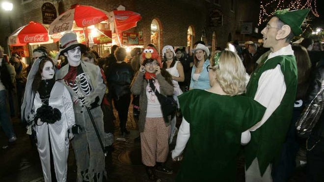 A couple dressed as elves passes a couple dressed as ghouls on Halloween in Salem, Mass., Wednesday Oct. 31, 2007.