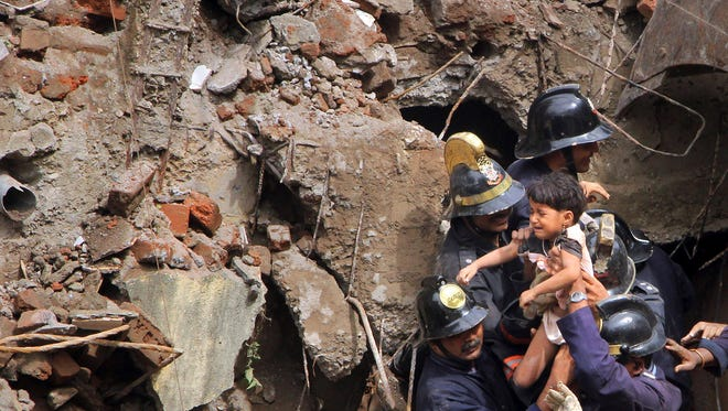 Indian emergency workers rescue a girl from debris of a collapsed building in Mumbai, India, on Friday.