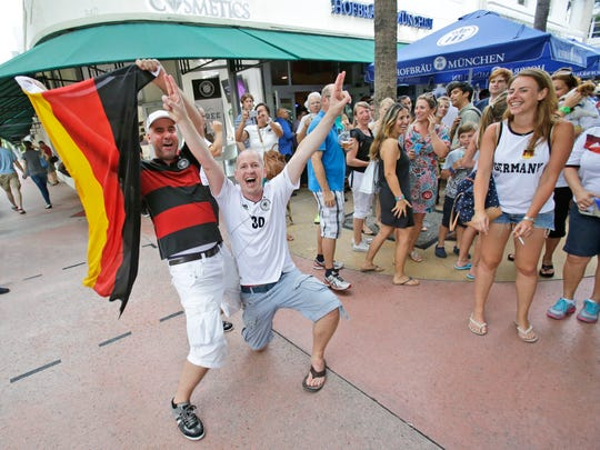 Ulf Roentgen, left, on vacation from Cologne, Germany, waves a German flag as he and Frank Neupert of Erfurt, Germany, celebrate Germany's win against Brazil during the World Cup semi final, after having watched the match outside the Hofbrau Beer Hall, Tuesday, July 8, 2014 in Miami Beach, Fla. (AP Photo/Wilfredo Lee)