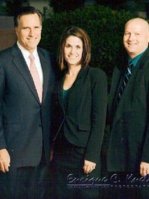 Anissa Ford, center, is shown posing next to Mitt Romney.