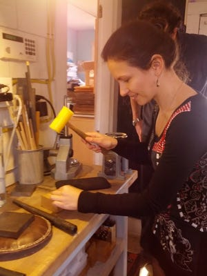 AT LEFT: Bride-to-be Yohana Voynova hammers her wedding band at the Heidi Lowe Gallery in Rehoboth.