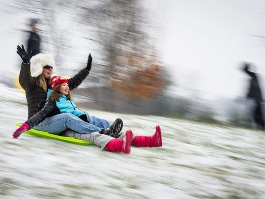 In this image taken with a slow shutter speed, Kristi Marion sleds with her 12-year-old daughter, Ella, at Hanes Park, Friday, Jan. 22, 2016, in Winston-Salem, N.C. A blizzard menacing the Eastern United States started dumping snow in Virginia, Tennessee and other parts of the South on Friday as millions of people in the storm's path prepared for icy roads, possible power outages and other treacherous conditions. (Andrew Dye/The Winston-Salem Journal via AP) MANDATORY CREDIT