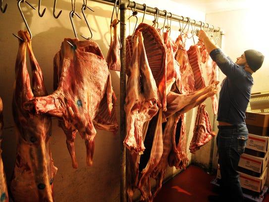 Botan Market owner Evan Tovi takes down some meat to
