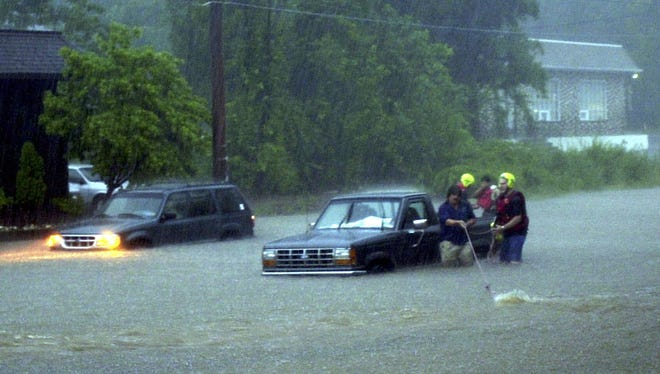 Rescue personnel assist a stranded motorist after floodwaters covered Horsham Road, Saturday, June 16, 2001, in Horsham, Pa. The National Weather Service had issued a flash flood watch for most of central and southeastern Pennsylvania.