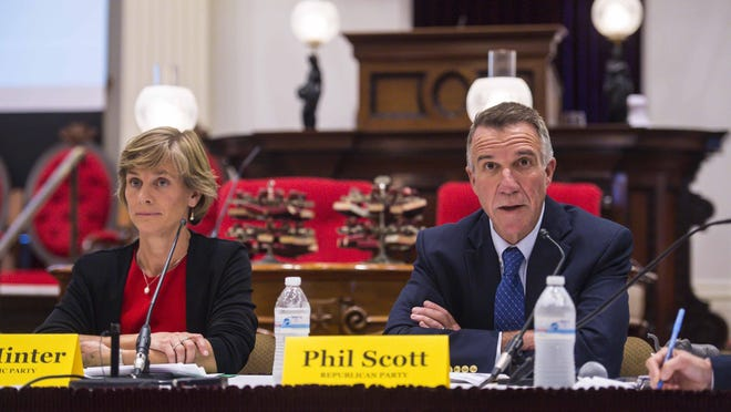 """Democratic candidate for governor Sue Minter, left, listens as Republican Lt. Gov. Phil Scott speaks during a gubernatorial debate at the Statehouse in Montpelier on Thursday, Sept. 22. Bill """"Spaceman"""" Lee of the Liberty Union party also participated."""