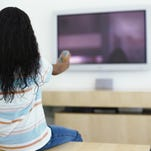 rear view of a girl pointing a remote to a television