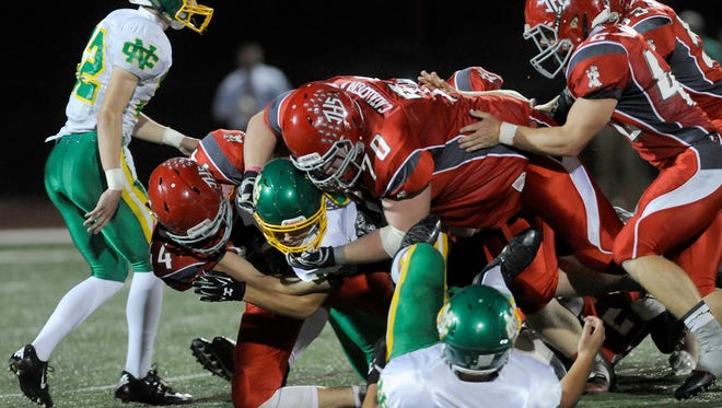 Johnstown's Hunter Alley (44) and Alex Catalogna (70) take down a Newark Catholic ball carrier during a game earlier this season.