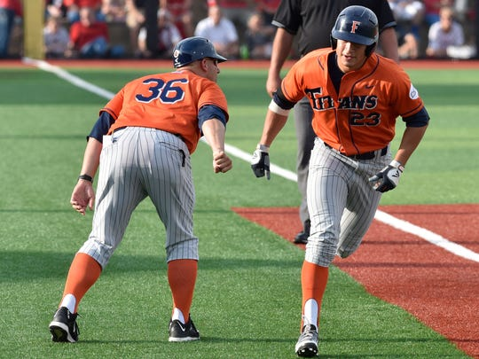 Cal State Fullerton's David Olmedo-Barrera, right, is congratulated by assistant coach Chad Baum following his solo home run during the first inning in a Super Regional-clinching win over Louisville on Monday.