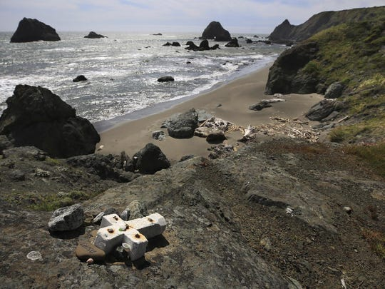 In this May 5, 2017 file photo, a memorial cross of stone for Lindsay Cutshall and her fiance, Jason Allen is bolted to a cliff above Fish Head Beach in honor of the two who were found murdered in 2004 just north of Jenner, Calif.