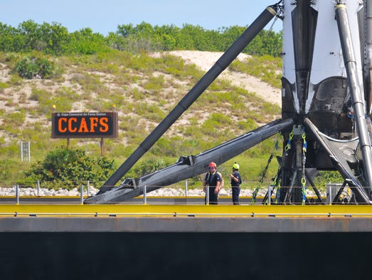 Crews work near the landing legs of SpaceX's Falcon