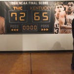 Tina Hill holds a portrait of her late husband, former 1966 Texas Western College championship team member Bobby Joe Hill, at an exhibit on the team inside the UTEP Union building Thursday. A photo of him is at center.