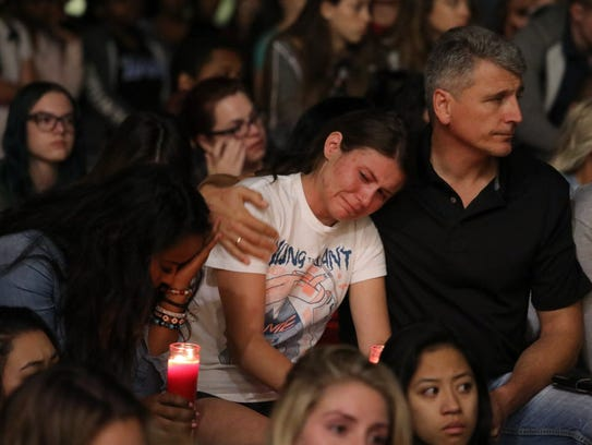 Mourners react during a candlelight vigil at the University