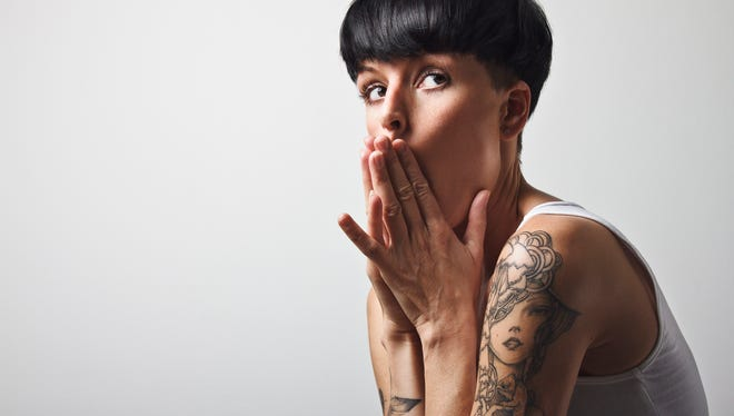 Woman with short black hair and tattoos