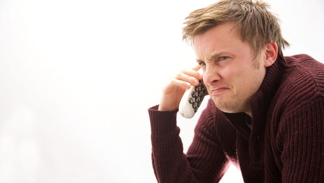 Young male making a telephone call looking unhappy
