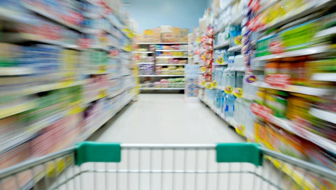 Shopping in supermarket shopping cart view with motion blur
