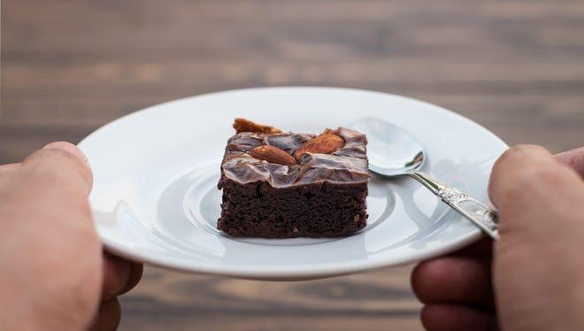 Homemade chocolate brownie with almond on hand