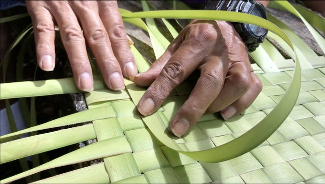 """Chamoru language teacher and weaver Joe """"Dagu"""" Babauta weaves a dining table mat using coconut leaves or fronds. Weaving, he said, has evolved from a survival skill to an form but he said the tradition has survived the test of times."""