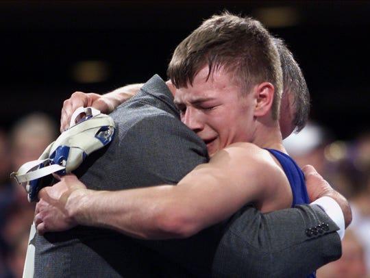 Jesse Sundell of Ogden hugs his coach after winning