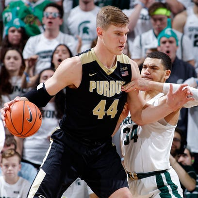Purdue's Isaac Haas, left, works for position against
