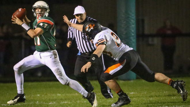 Berlin quarterback Carter Jodarski (17) rolls out under pressure to pass. The Berlin Indians hosted the Ripon Tigers Friday night, October 9, 2015.