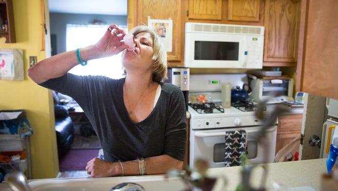 Julie Polizzi takes her daily dose of methadone at her home in Rochester on Jan. 7, 2016. Polizzi started using street drugs like heroin in her 30s to deal with pain after surviving stage four cervical cancer. She now takes methadone to help with her addiction and pain.