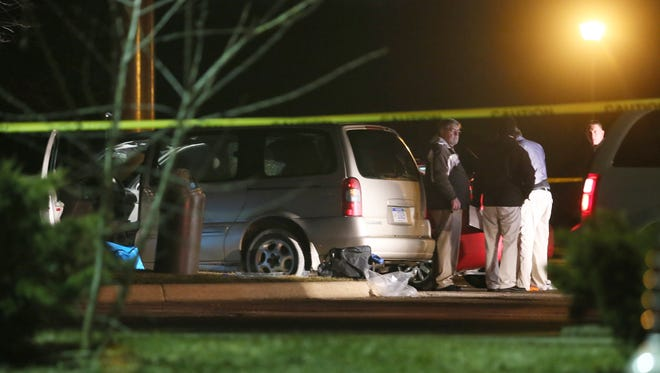 Police investigate the scene early Feb. 21, 2016, where people were shot in vehicles outside a Cracker Barrel restaurant in Kalamazoo, Mich.