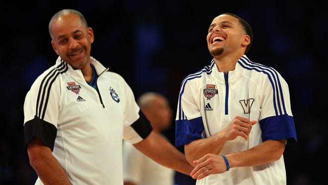 Stephen Curry of the Golden State Warriors jokes with his father, former NBA standout Dell Curry, during the 2015 Shooting Stars Competition as part of the NBA All-Star Weekend.