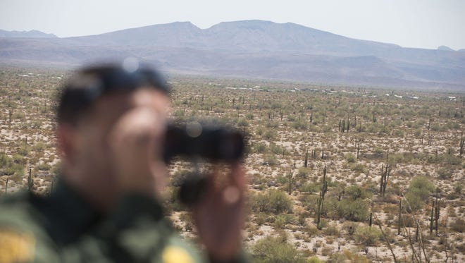 Agent Daniel Hernandez of the U.S. Border Patrol looks for traces of a person who was illegally crossing the U.S. border near Ajo.