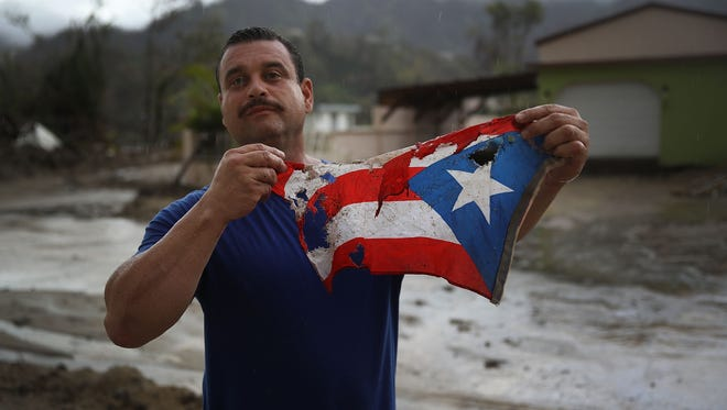 Jose Javier Santana holds a Puerto Rican flag he found on the ground after Hurricane Maria passed through Oct. 6, 2017 in Utuado, Puerto Rico.