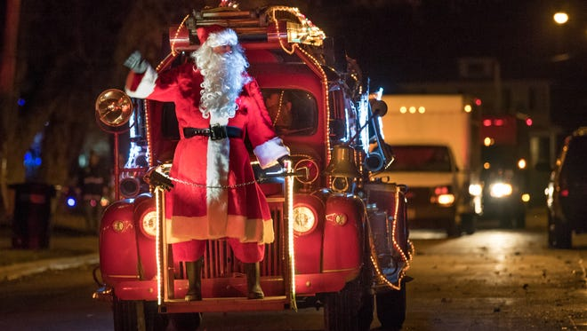 Santa waves during the 18th annual Oshkosh Fire Department's Food and Toy Drive in this 2016 file photo.