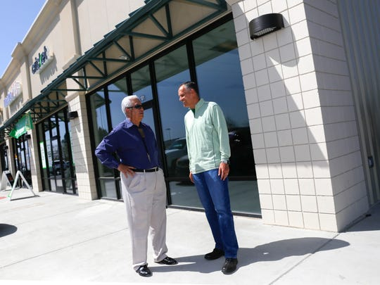 Navajo Plaza investor Steve Arias, left, and Farmington Mayor Tommy Roberts talk Wednesday after a ribbon-cutting ceremony at the Farmington Crossing shopping center.