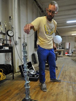 Wausau sculptor Keith Kaziak points to one of his abstract sculptures. He used Marathon County clay to make a mold for the piece.