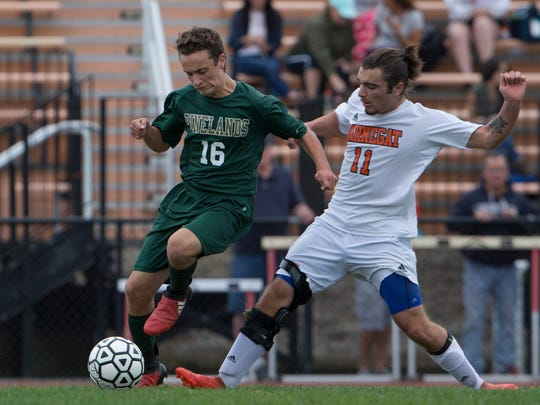 Pinelands' Tyler Piazza and Barnegat's Rick Norman battle for a ball during first half action. Pinelands Boys Soccer vs Barnegat in Barnegat, NJ, on October 11, 2017.