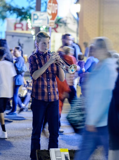 Stephen Roy, 16, of Peoria, plays various Christmas Carols on his trumpet at the Glendale Glitters Spectacular Weekend on Friday, Nov. 24, 2017, at Murphy Park in downtown Glendale, Ariz.