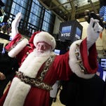 Santa Claus, from the Macy's Thanksgiving Day Parade, visits the trading floor of the New York Stock Exchange before the opening bell, Wednesday, Nov. 25, 2015. (AP Photo/Richard Drew)